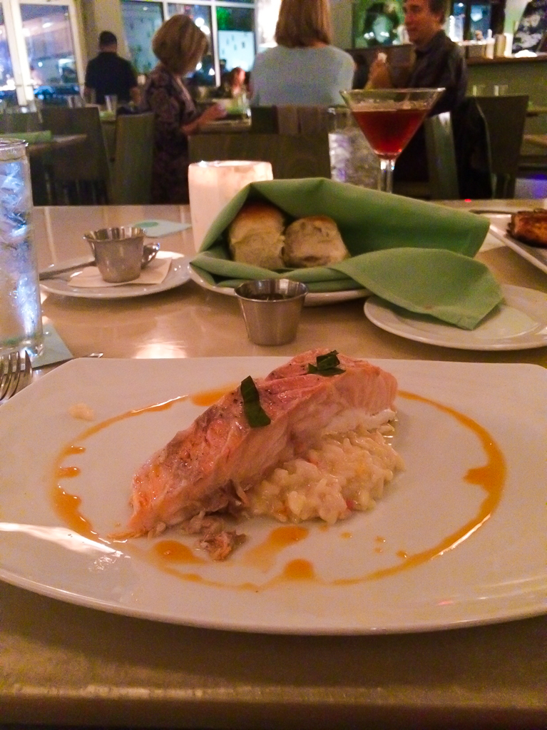 Dinner at Reef. Slow Baked Salmon served over meyer lemon risotto and chili oil.